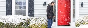 snow covered shrubs with man standing on home porch